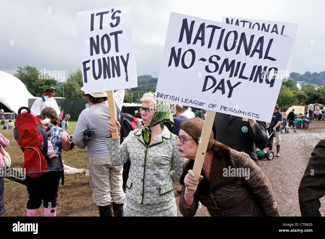 Grumpy Glastonbury Festival performance artists demonstrate for a National No-Smiling Day - Stock Image