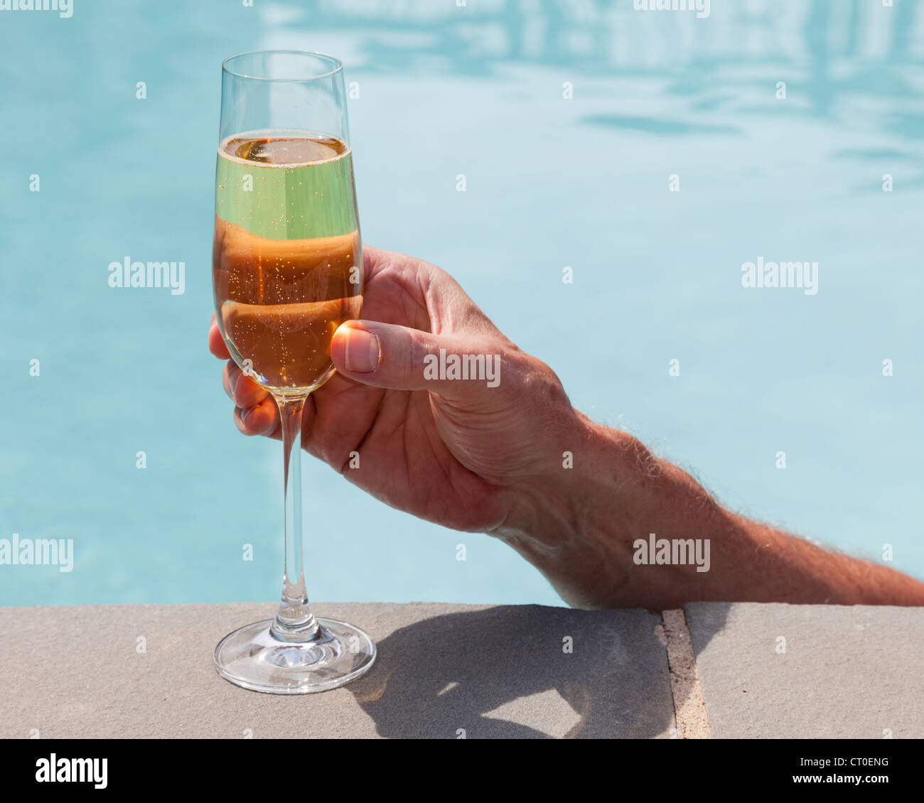 Man drinking champagne / wine while in the swimming pool - Stock Image