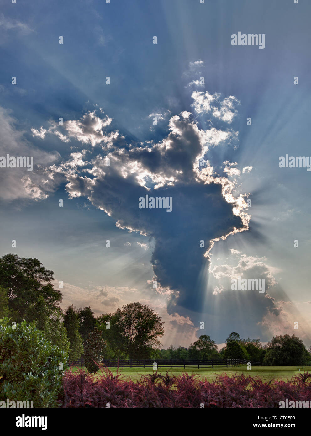 Storm clouds over meadows with sunrays, dramatic sky - Stock Image