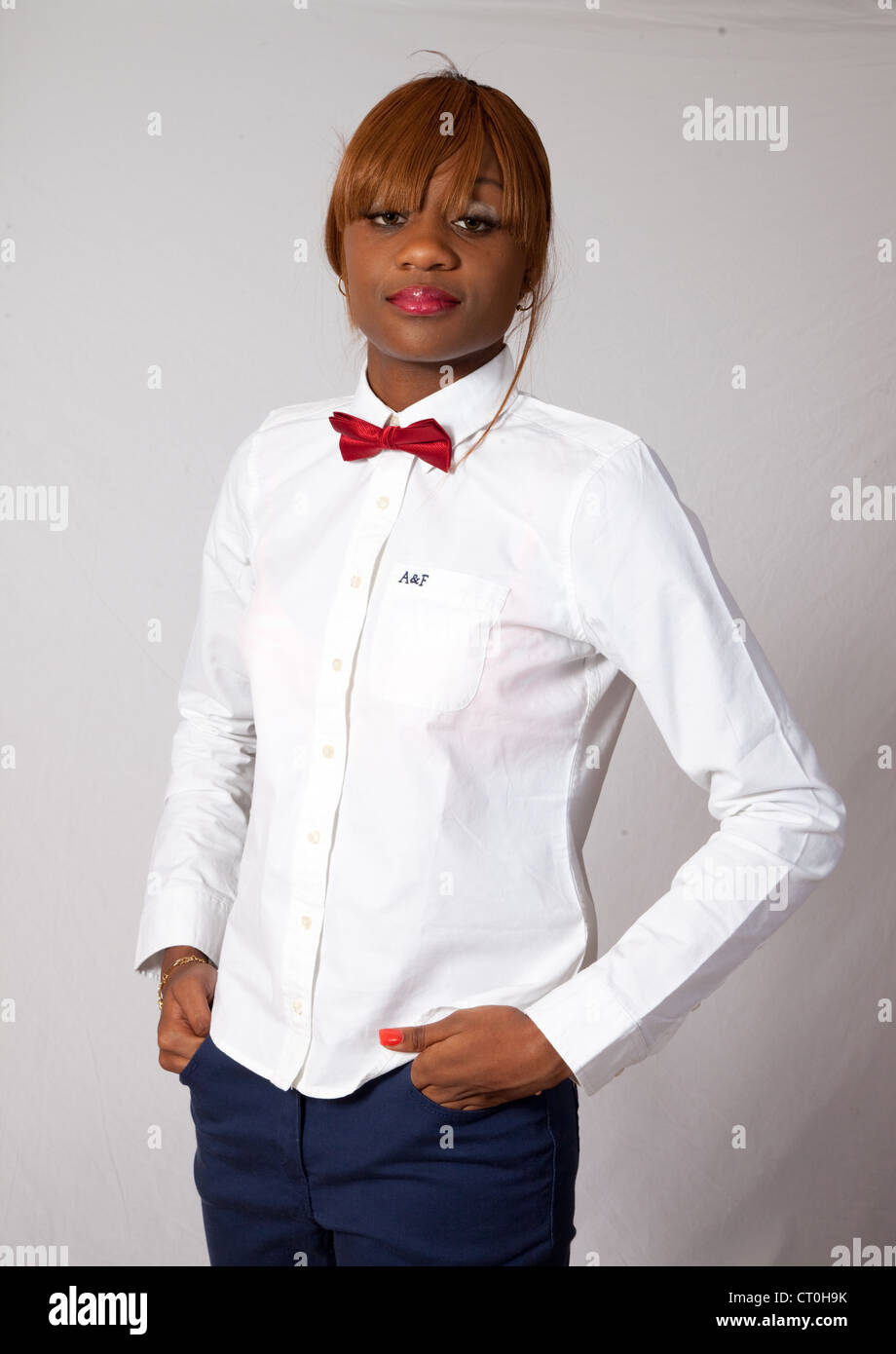 Lovely Black Woman In White Shirt Red Bow Tie And Blue Pants Stock