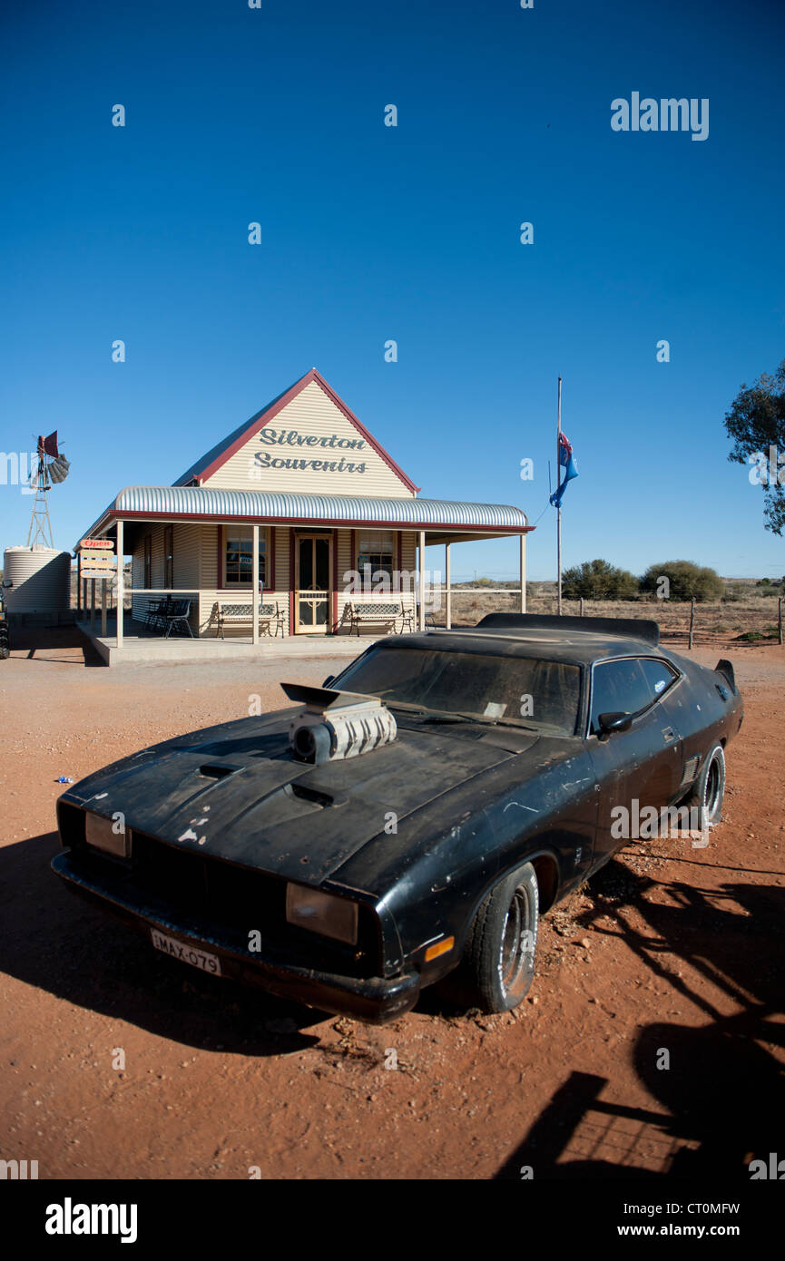 The film car of Mad Max 2 parked in front of an old homestead now shop in Silverton, outback New South Wales - Stock Image