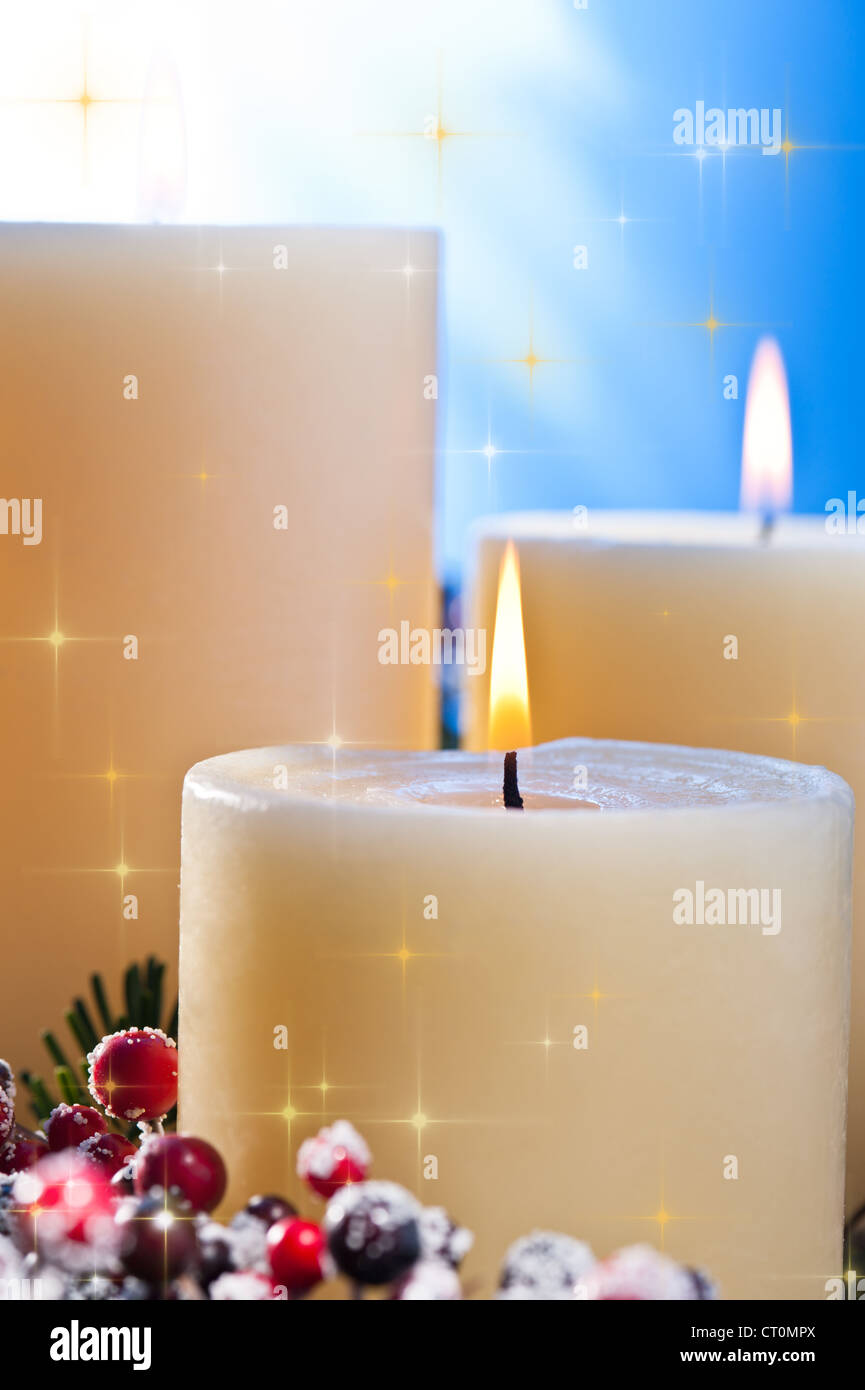 Three candles in an advent flower arrangement for advent and Christmas with golden stars Stock Photo