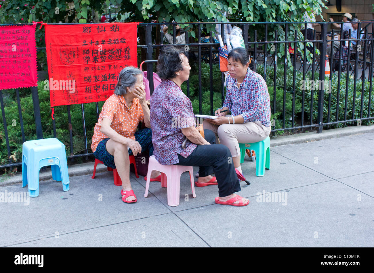 Two Asian women consulting a fortune teller in Chinatown in New York City - Stock Image