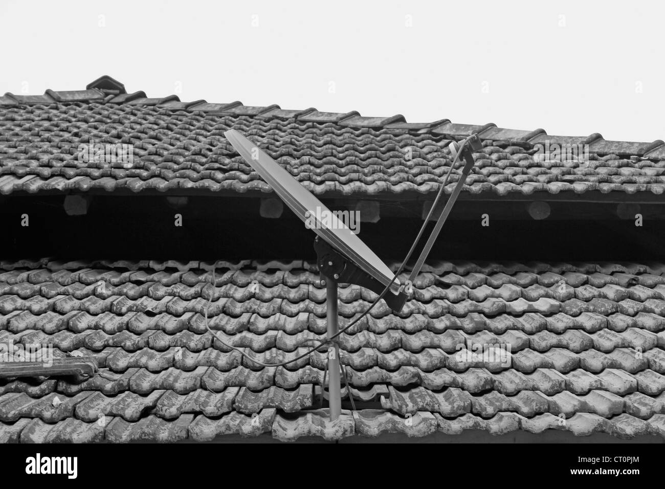 A dish antenna of a television set on a Traditional sloping roof made with Manglori tiles, Ratnagiri, Maharashtra, - Stock Image
