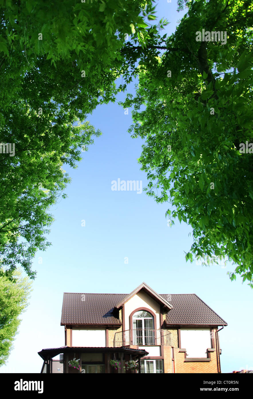 Beautiful house under the arch of trees in the background of the summer sky. - Stock Image