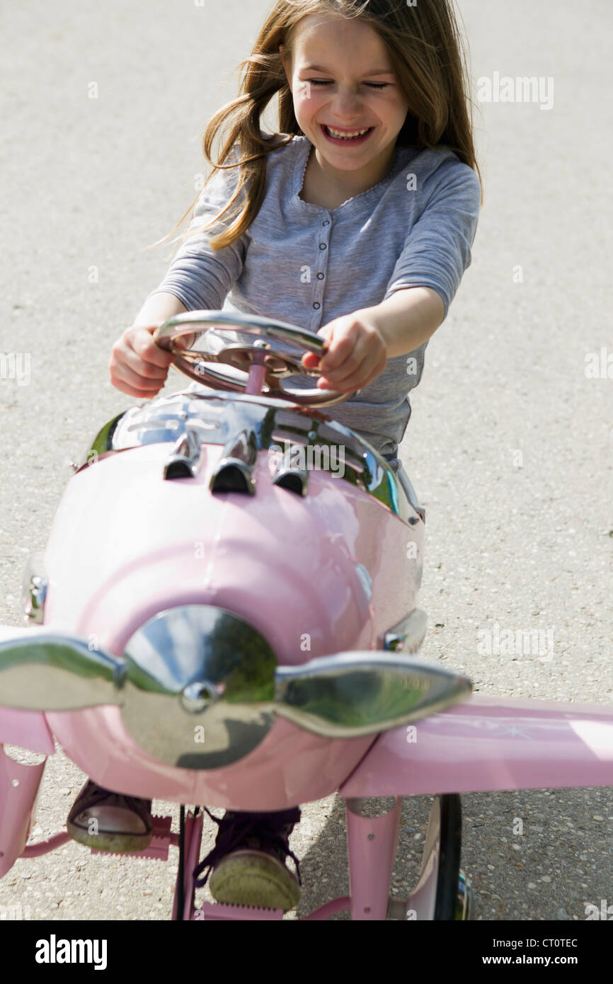 Smiling girl driving toy airplane - Stock Image