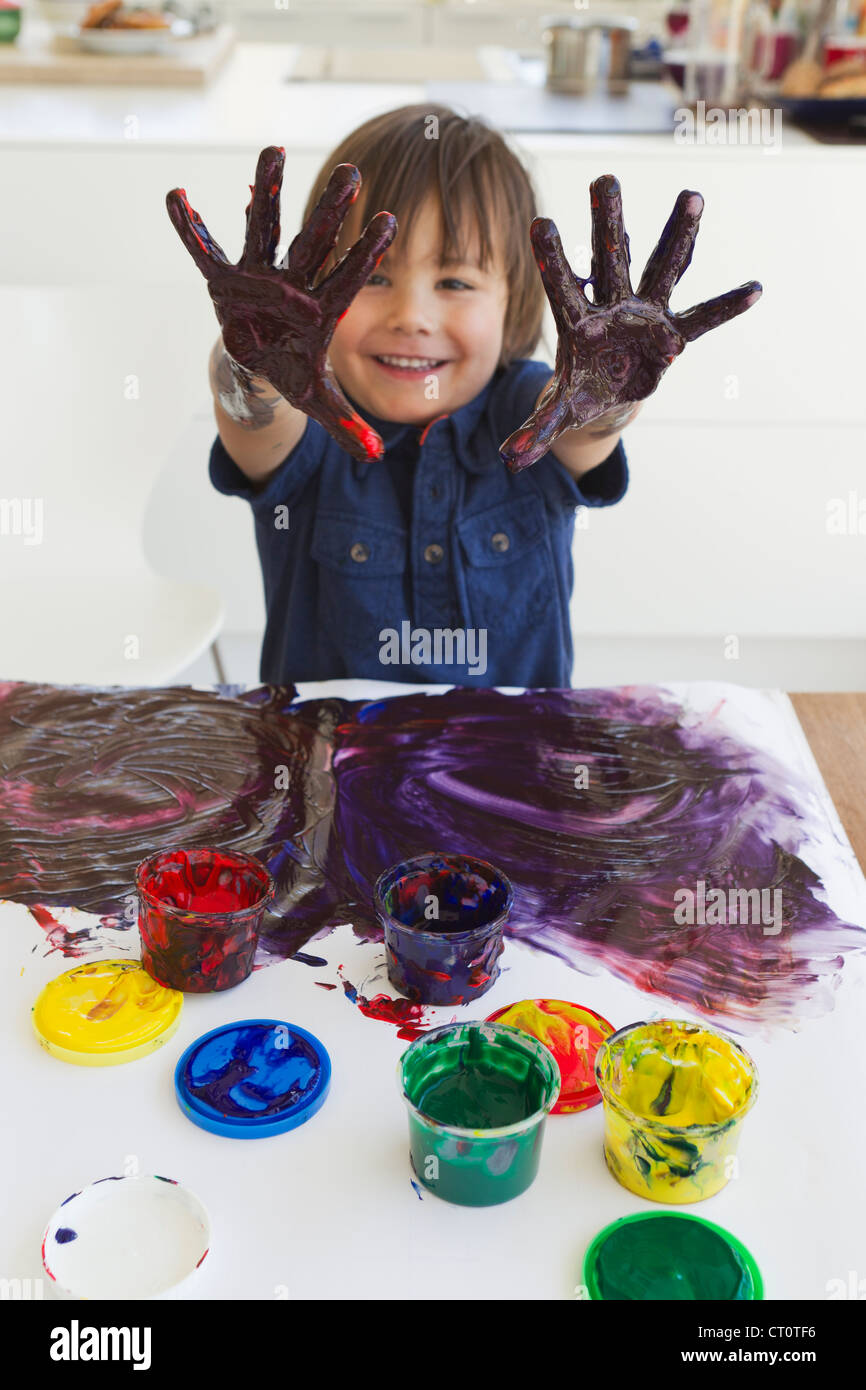 Boy finger painting on paper Stock Photo