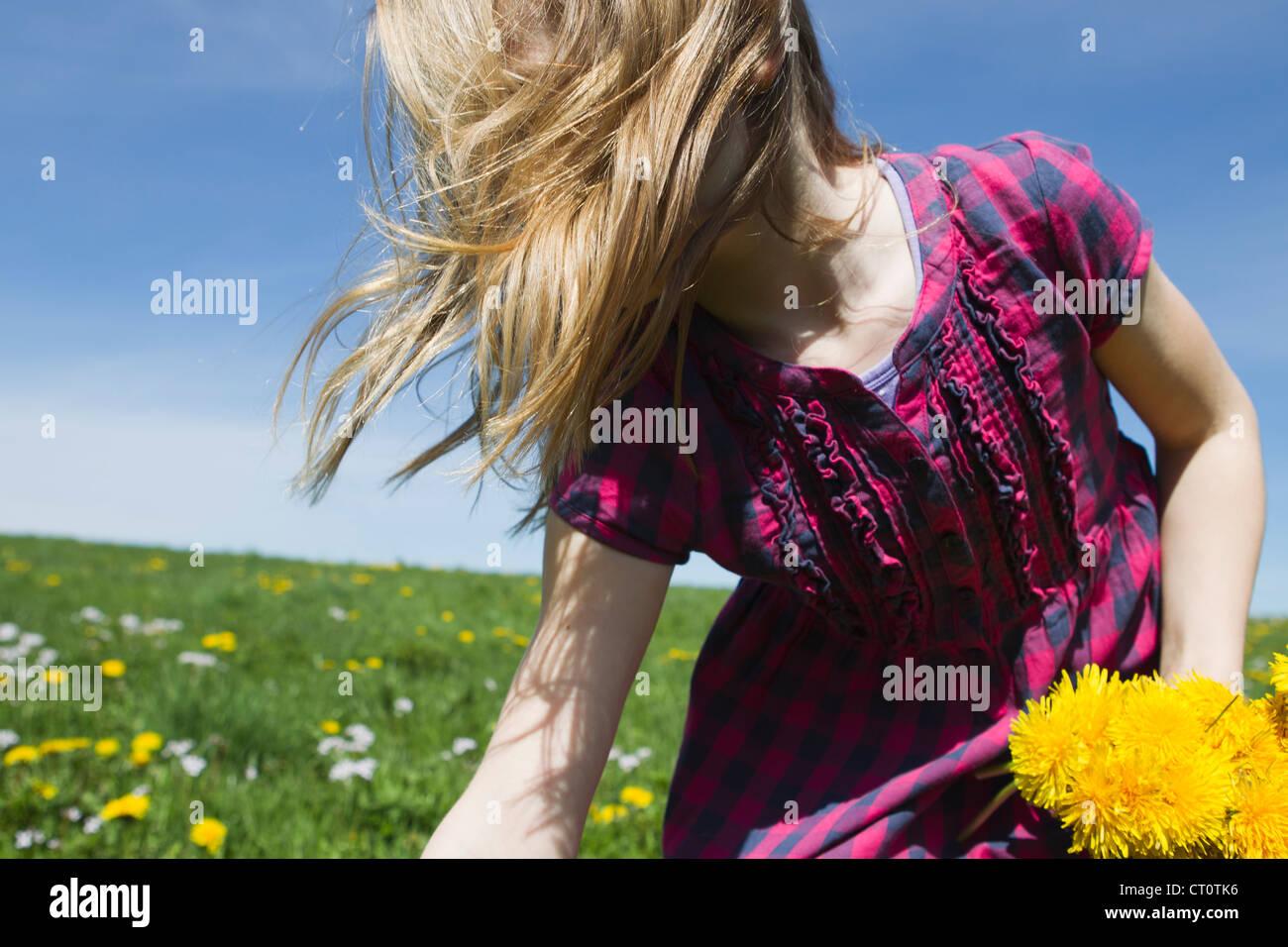 Girl picking wildflowers in field Stock Photo