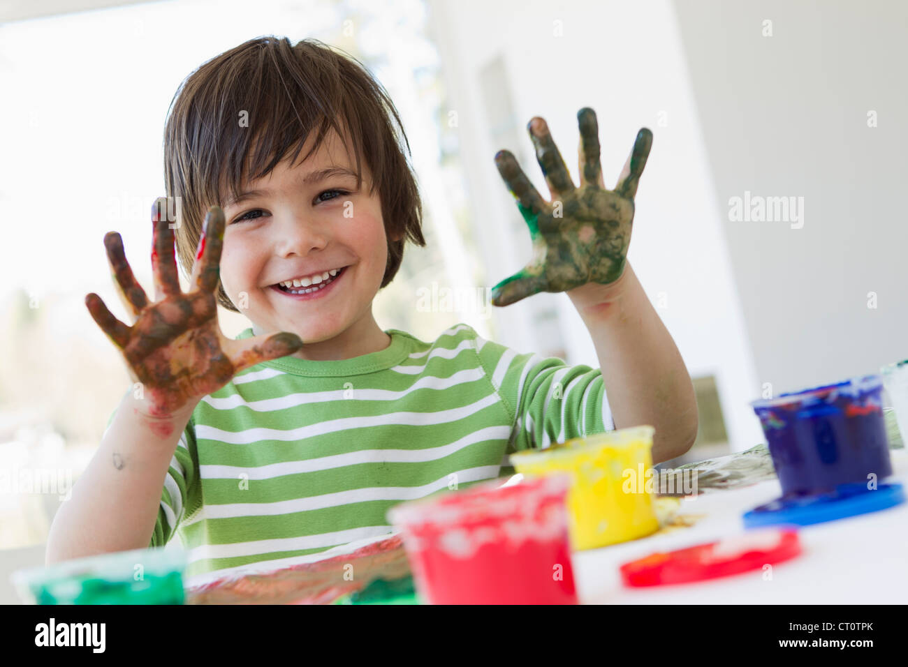 Smiling boy finger painting indoors - Stock Image