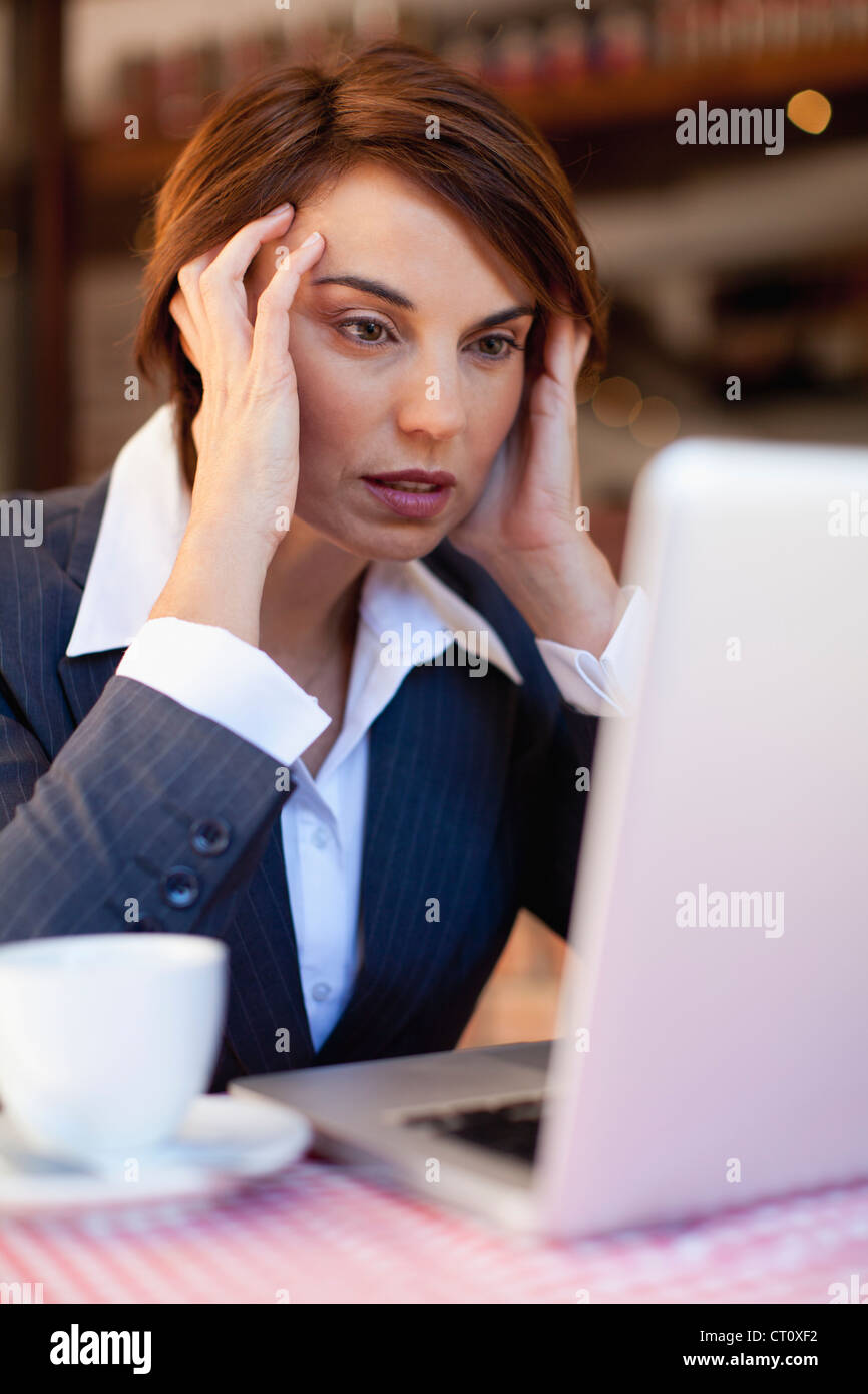 Stressed businesswoman working in cafe - Stock Image