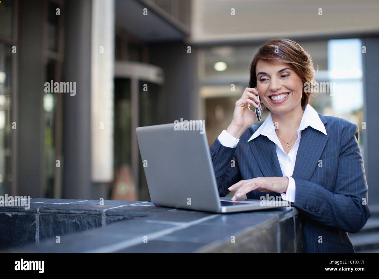 Businesswoman using laptop outdoors - Stock Image