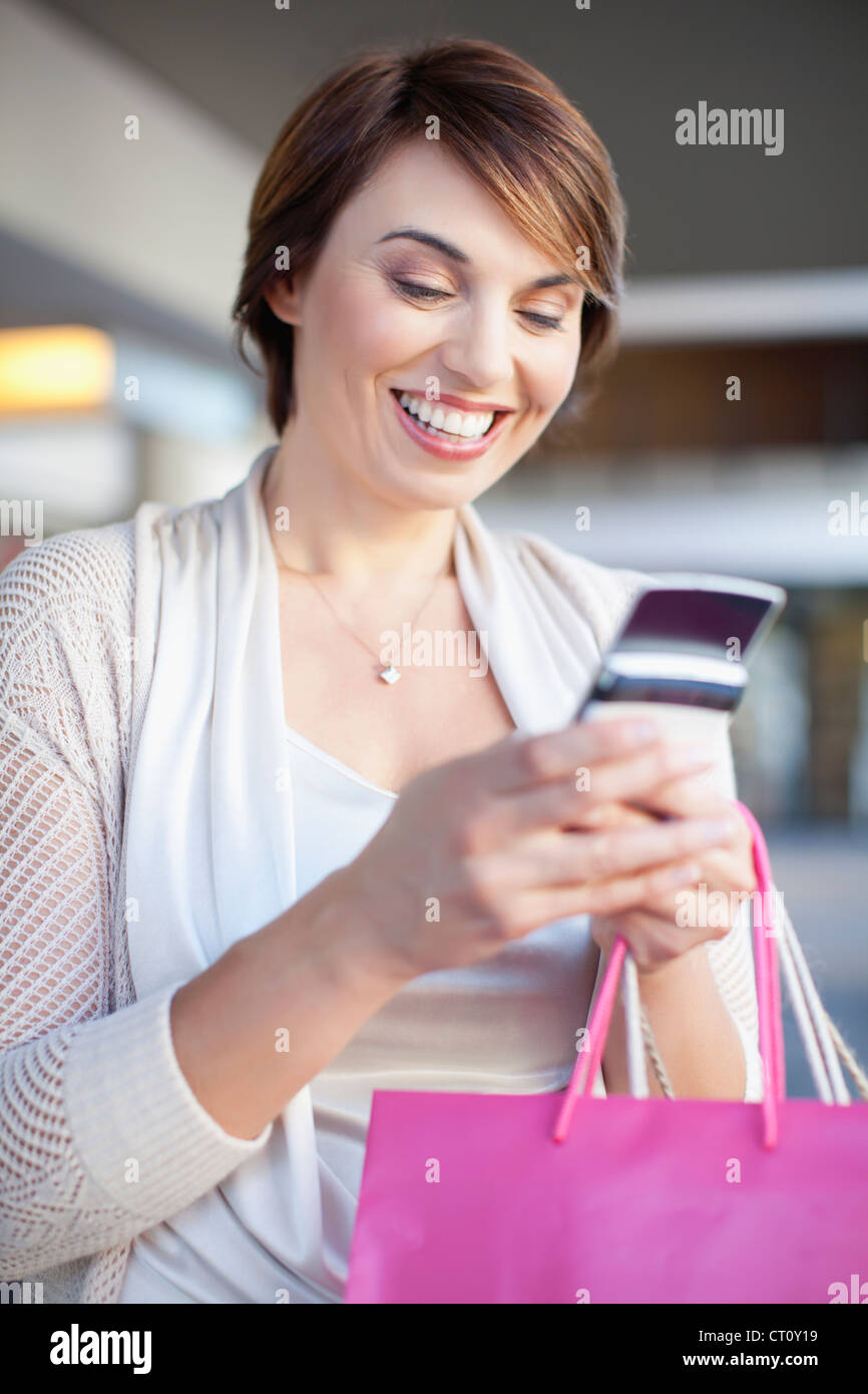Woman using cell phone on city street Stock Photo