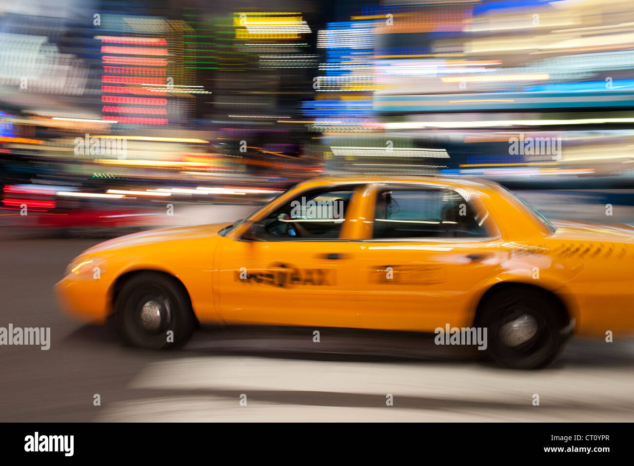 Motion-blurred image of a yellow New York cab driving in Manhattan at night. - Stock Image
