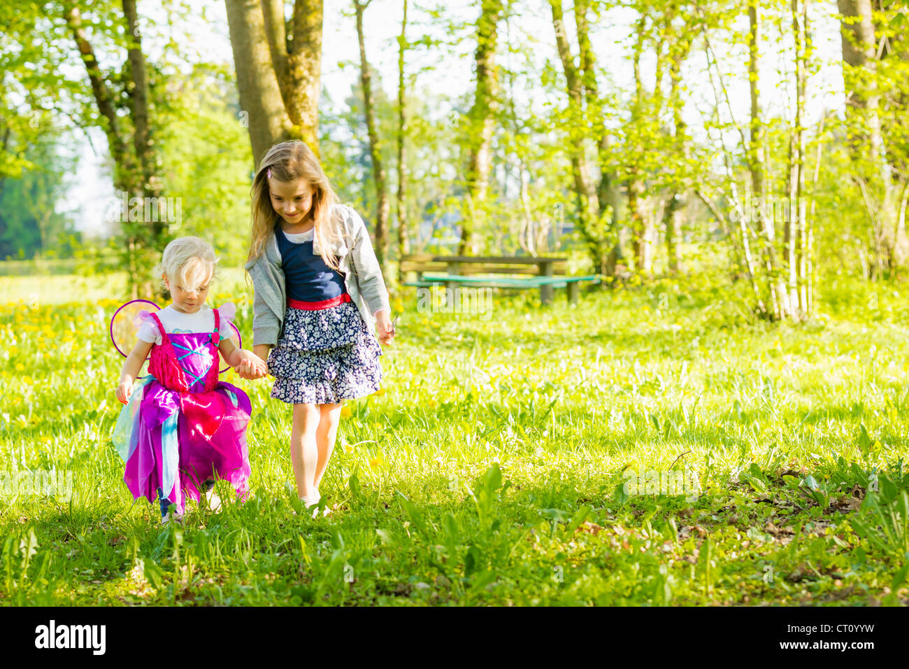 Girls walking together in field - Stock Image