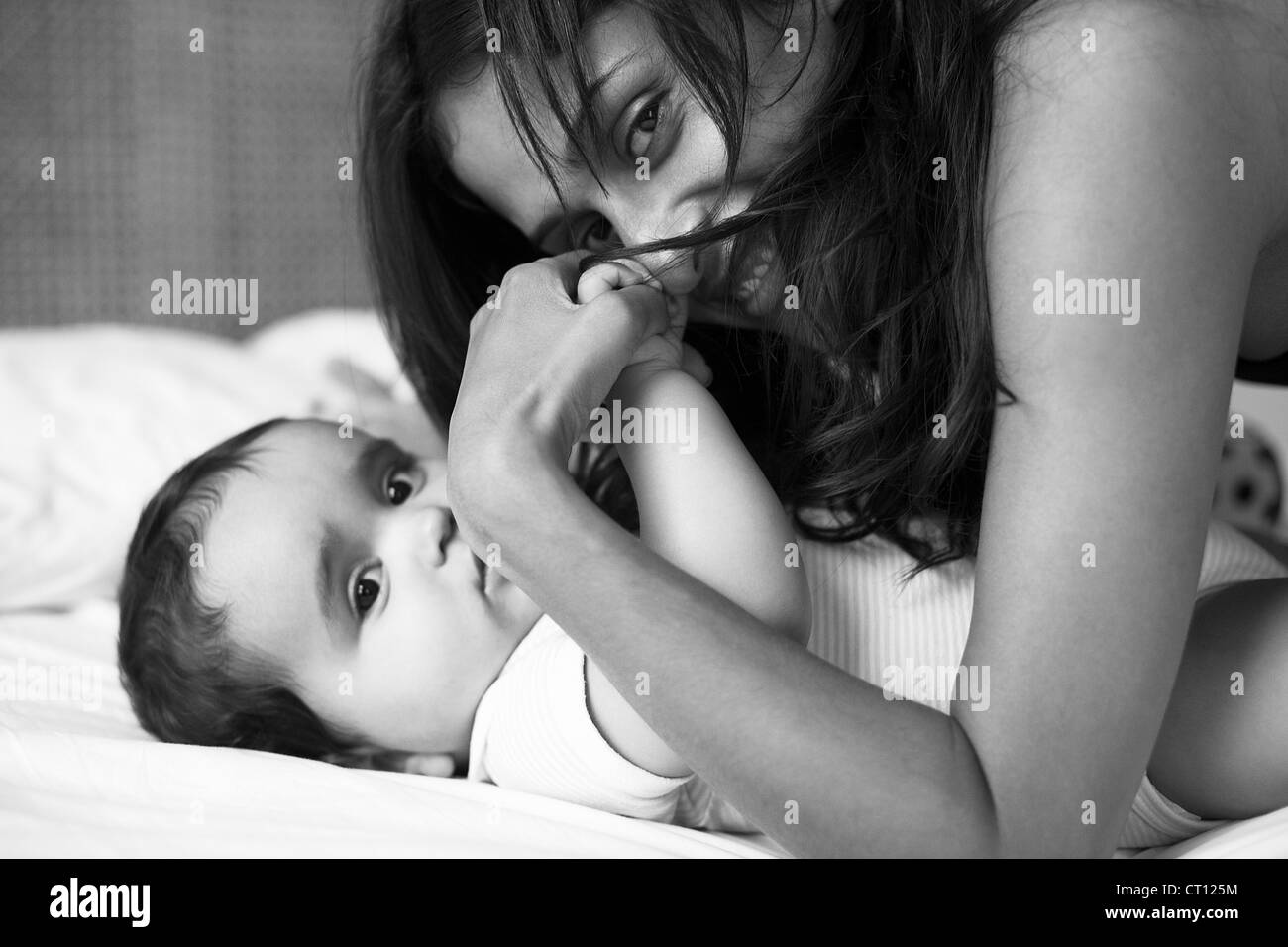 Mother and baby laying on bed - Stock Image