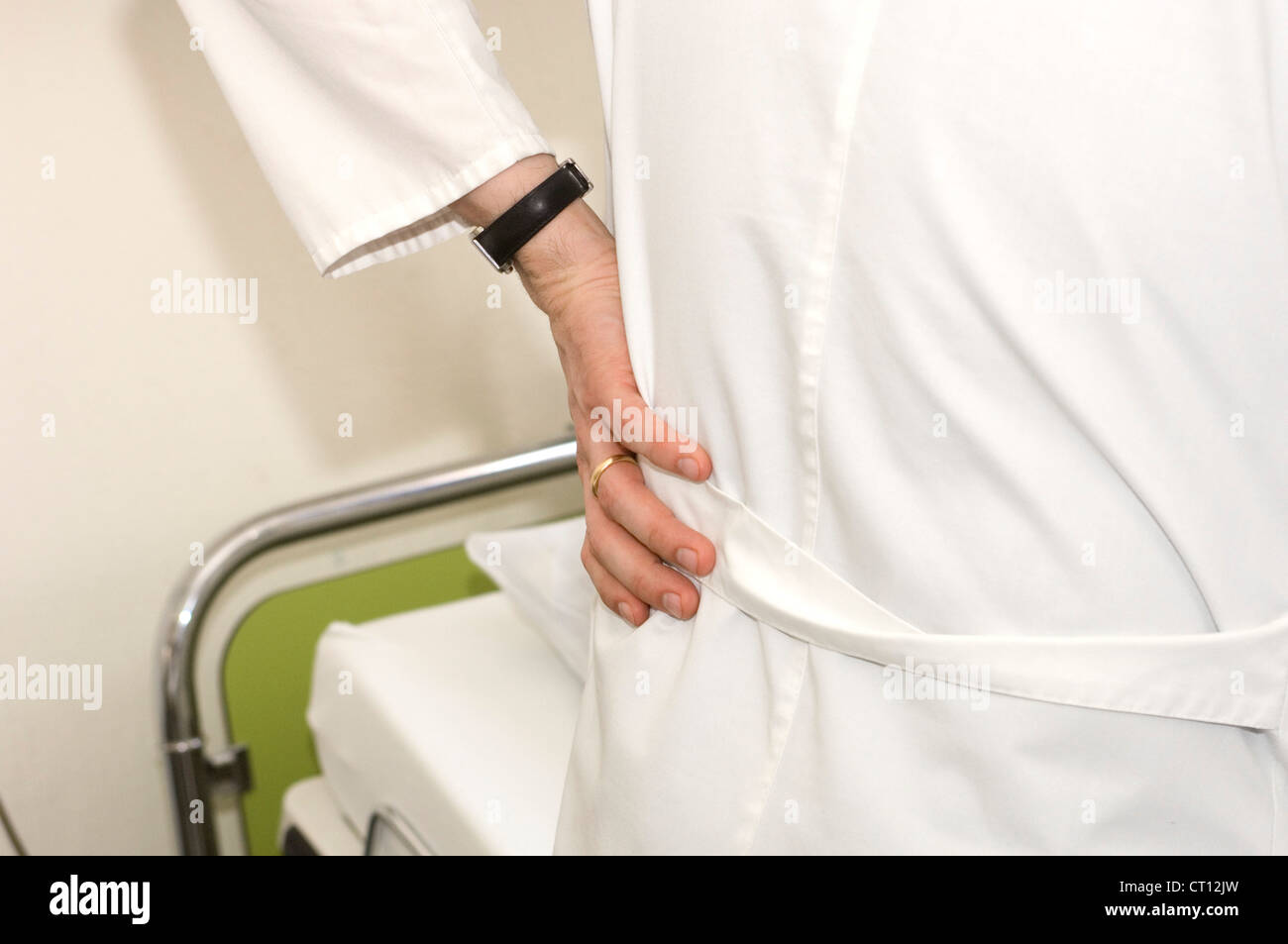 Hand on hip, a doctor at the hospital bedside of a patient. - Stock Image