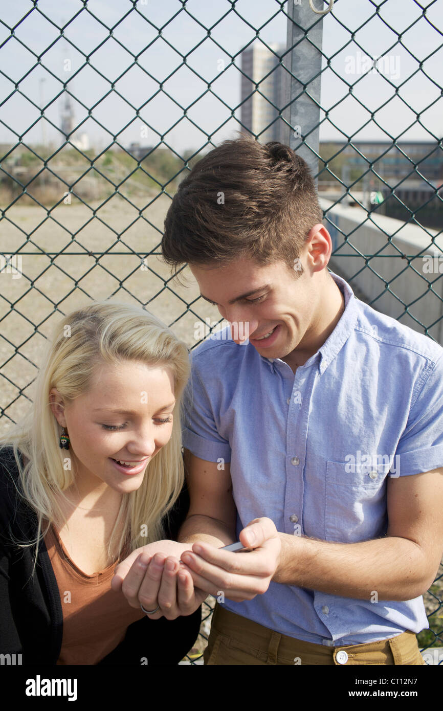 Couple using cell phone on city street Stock Photo