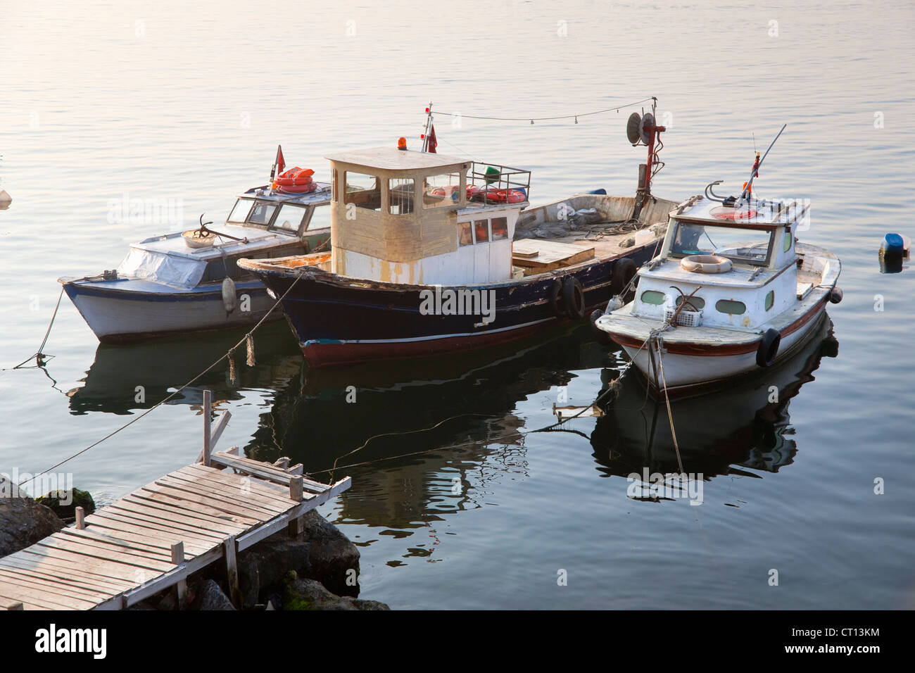 Tugboats docked at pier - Stock Image