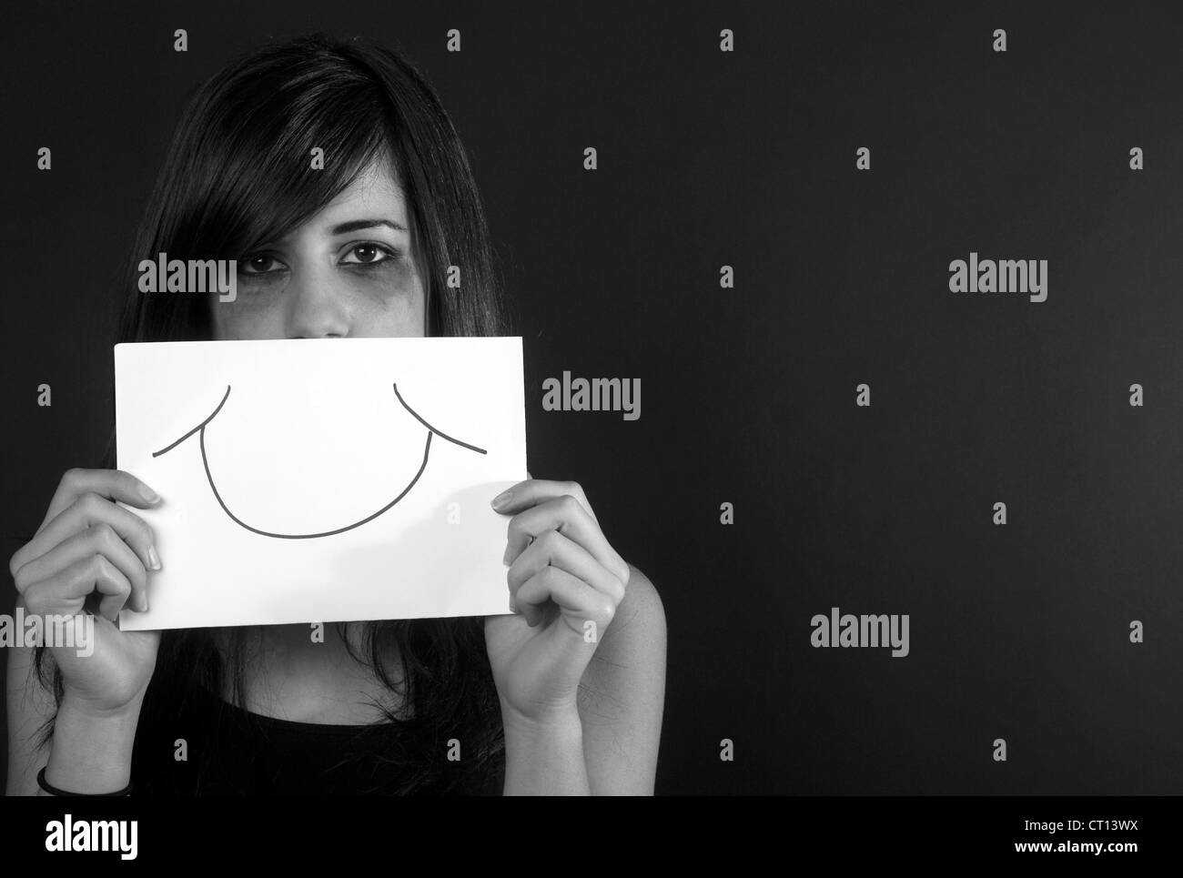 Crying teenage girl holding fake smile - Stock Image