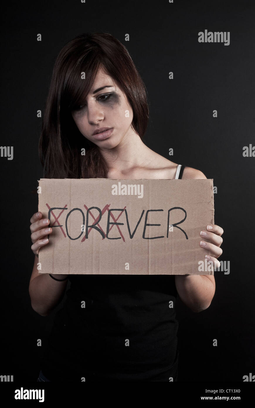 Crying teenage girl holding over sign - Stock Image