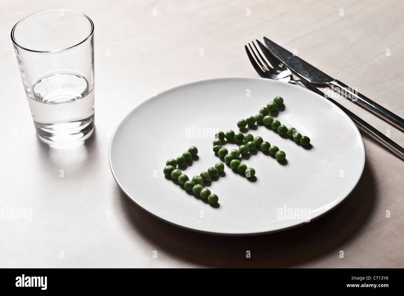 Peas arranged to spell fat on plate - Stock Image