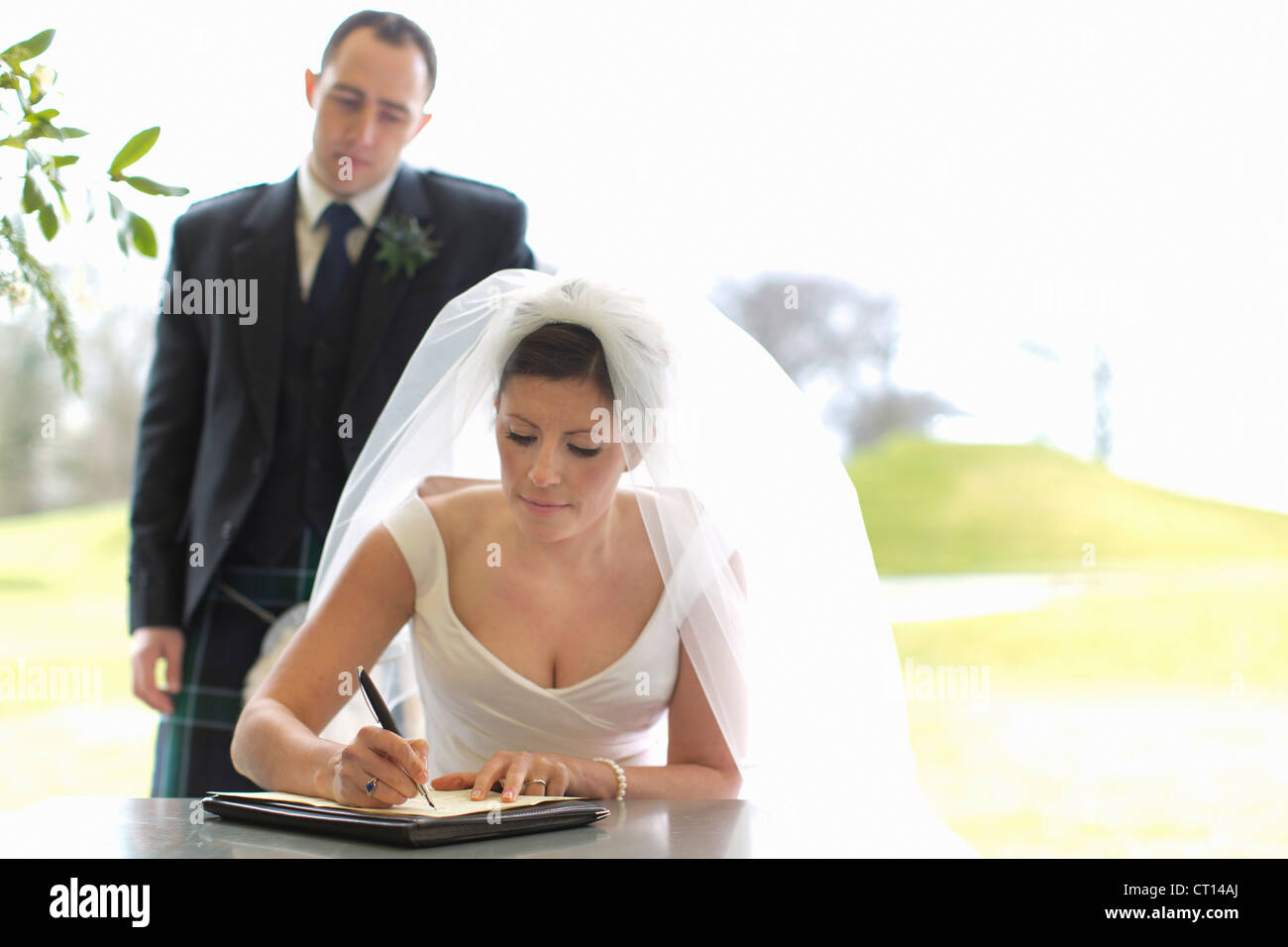 Newlywed couple signing marriage license - Stock Image