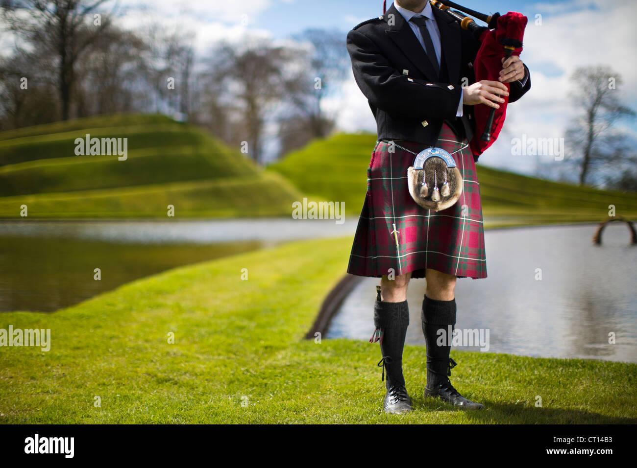 Man in Scottish kilt playing bagpipes - Stock Image