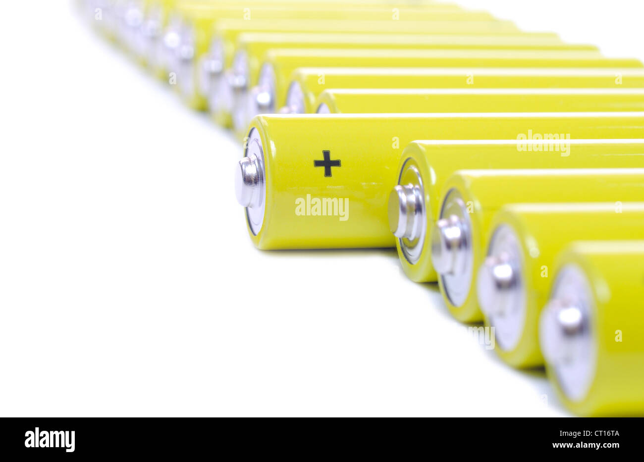 yellow batteries in a row on white - Stock Image