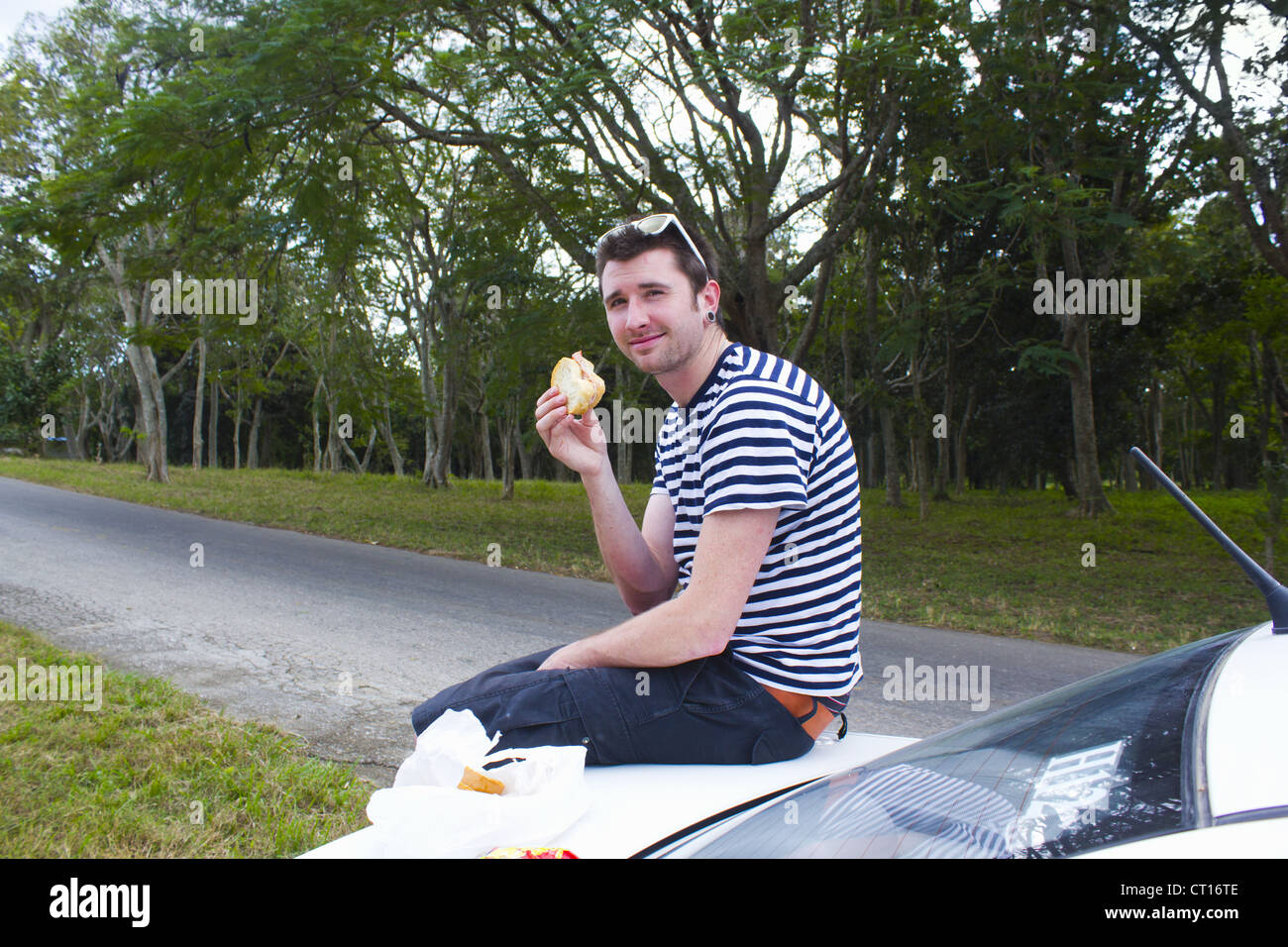 Man eating sandwich on trunk of car - Stock Image