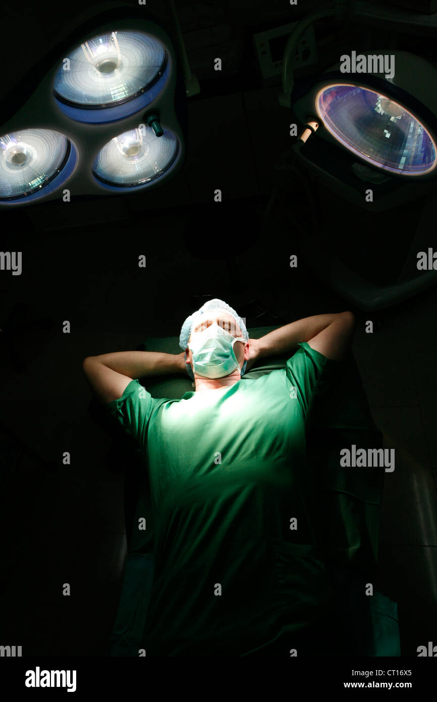 A tired Surgeon sleeps on an operating table with his hands behind his head. - Stock Image