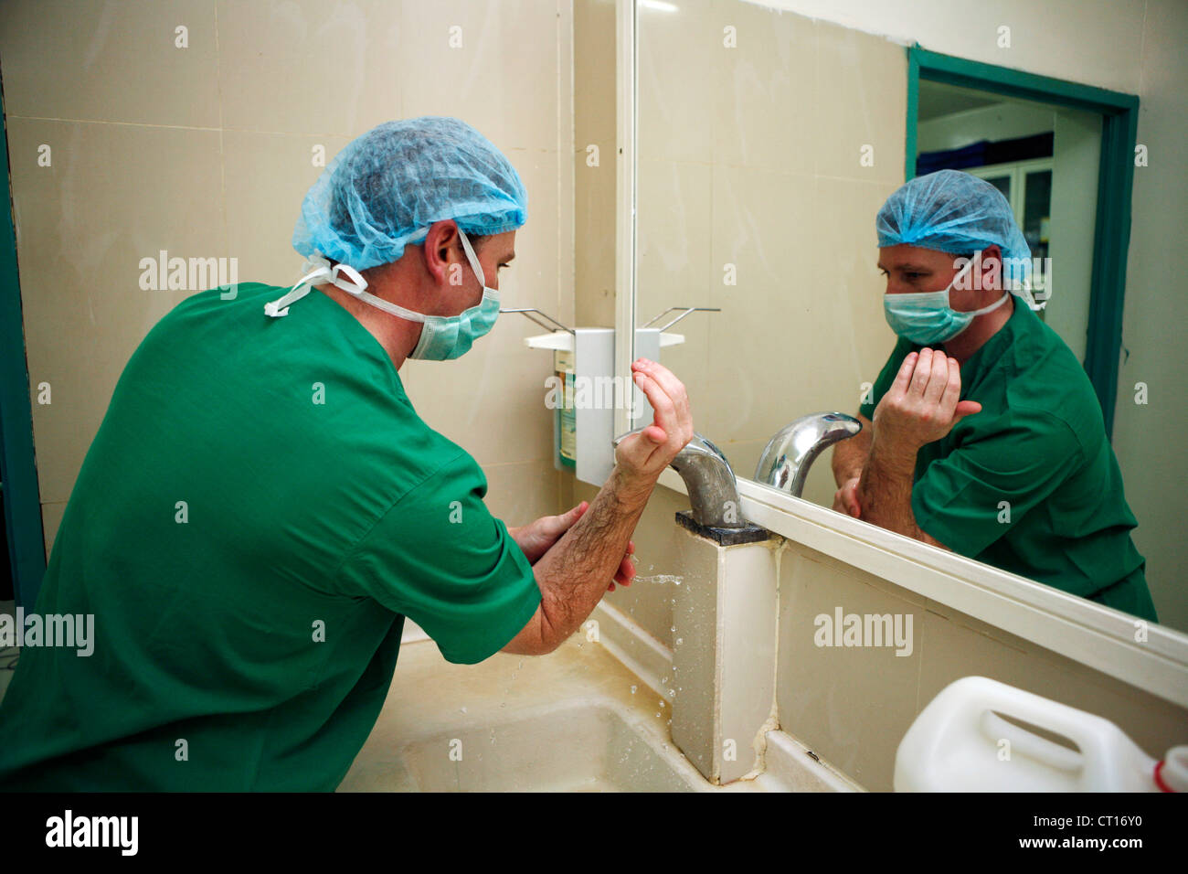 A Surgeon washes his hands and arms prior to surgery. - Stock Image