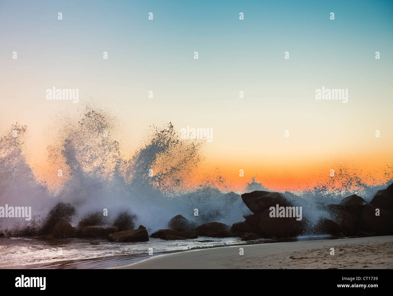 Waves crashing on rocky beach at sunset - Stock Image