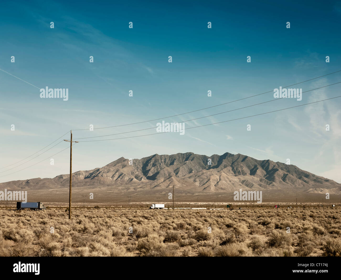 Power lines, dirt road and mountain - Stock Image