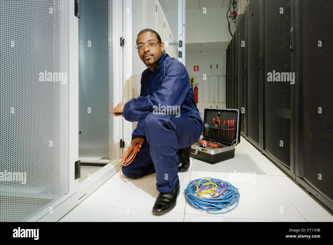 Technician working in server room - Stock Image
