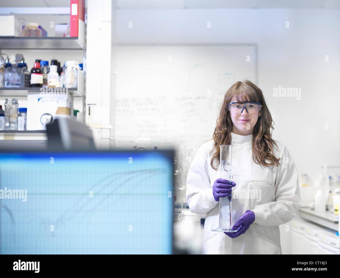 Scientist carrying beaker in lab - Stock Image