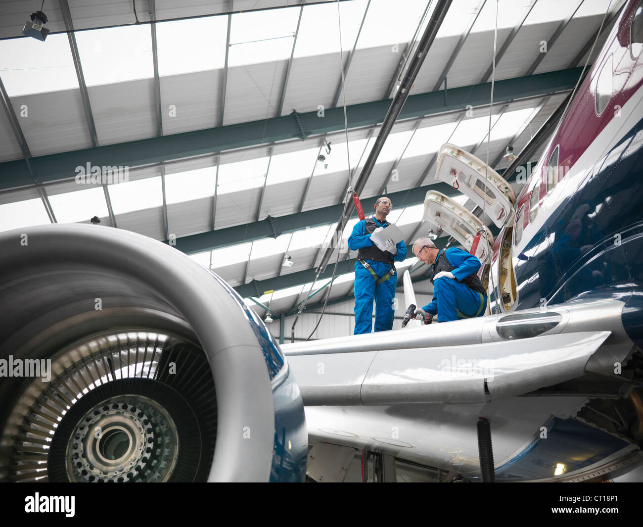 Workers examining airplane wing - Stock Image