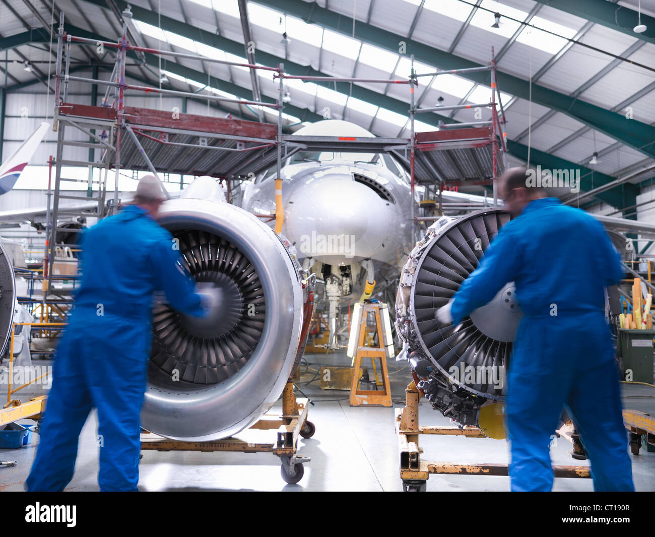 Worker pushing airplane engines on carts - Stock Image