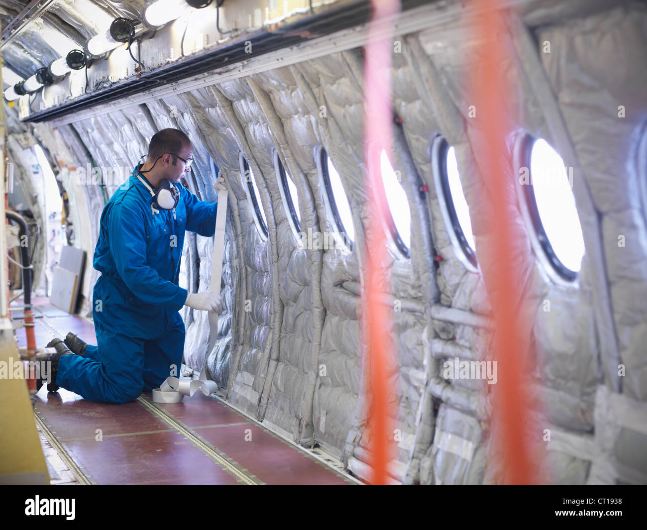Worker measuring airplane window - Stock Image