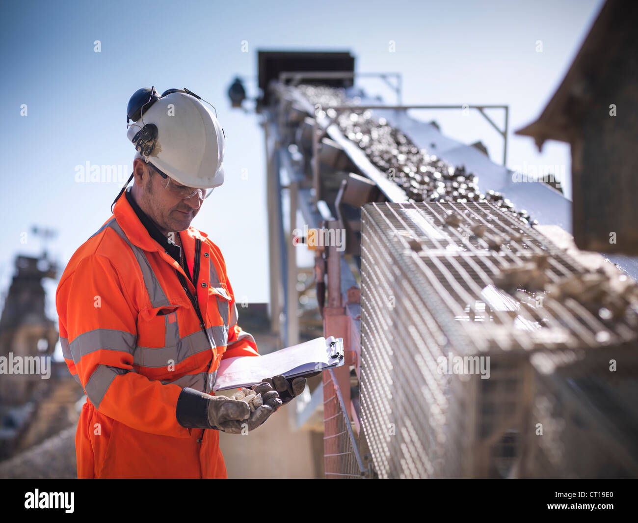 Worker with clipboard by conveyor belt - Stock Image