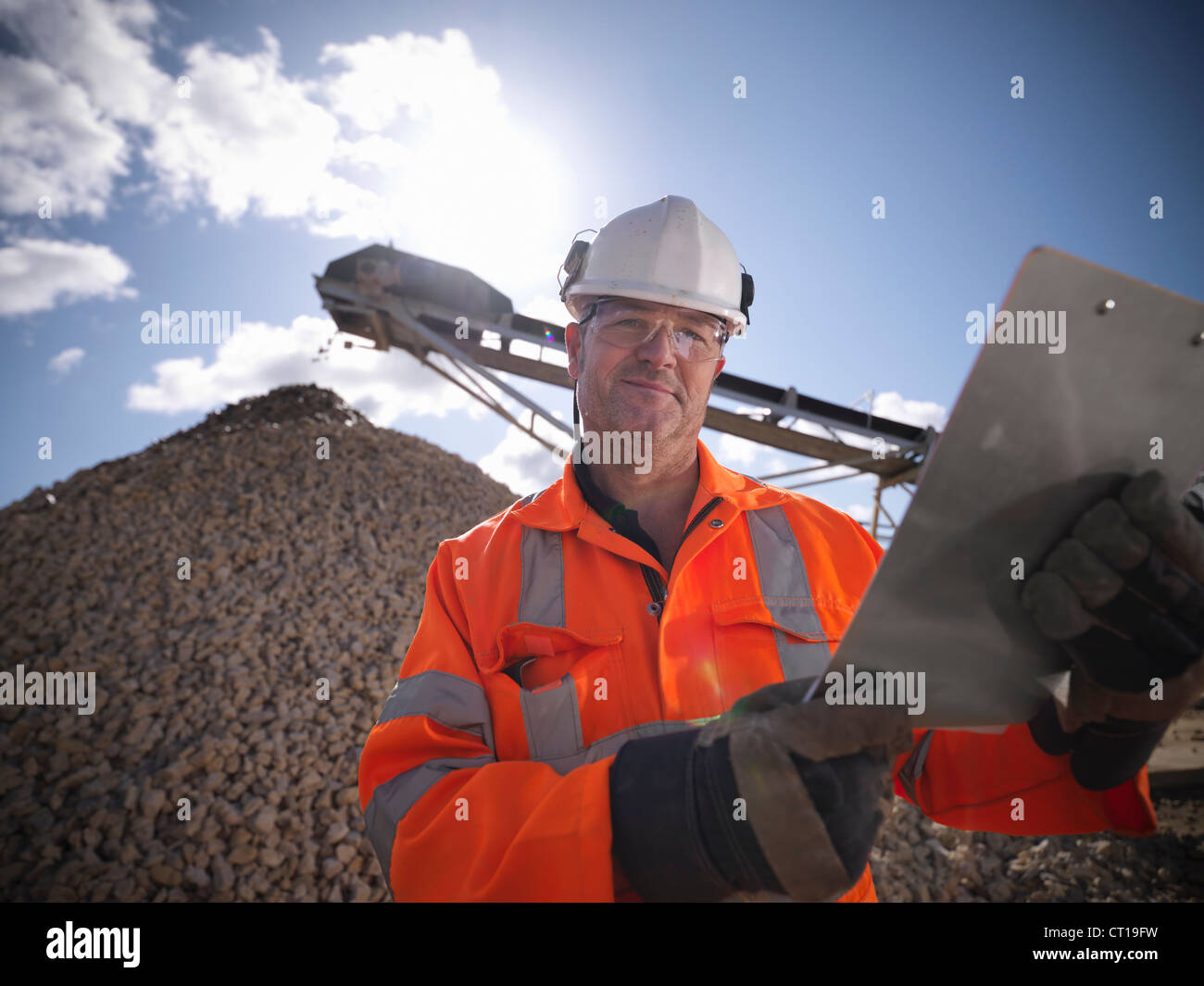 Worker standing by pile of stones - Stock Image