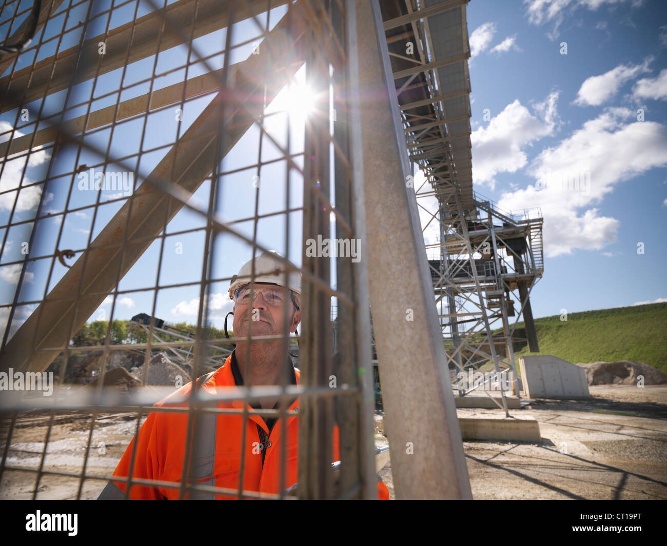 Worker standing under conveyor in quarry - Stock Image