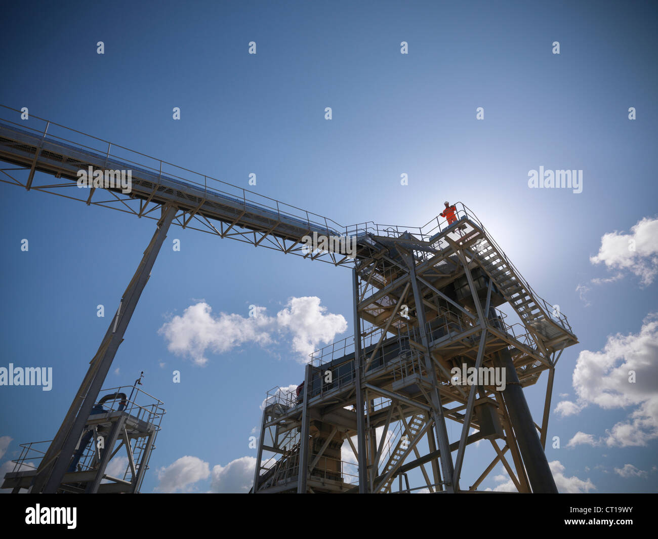 Worker standing on conveyor in quarry - Stock Image