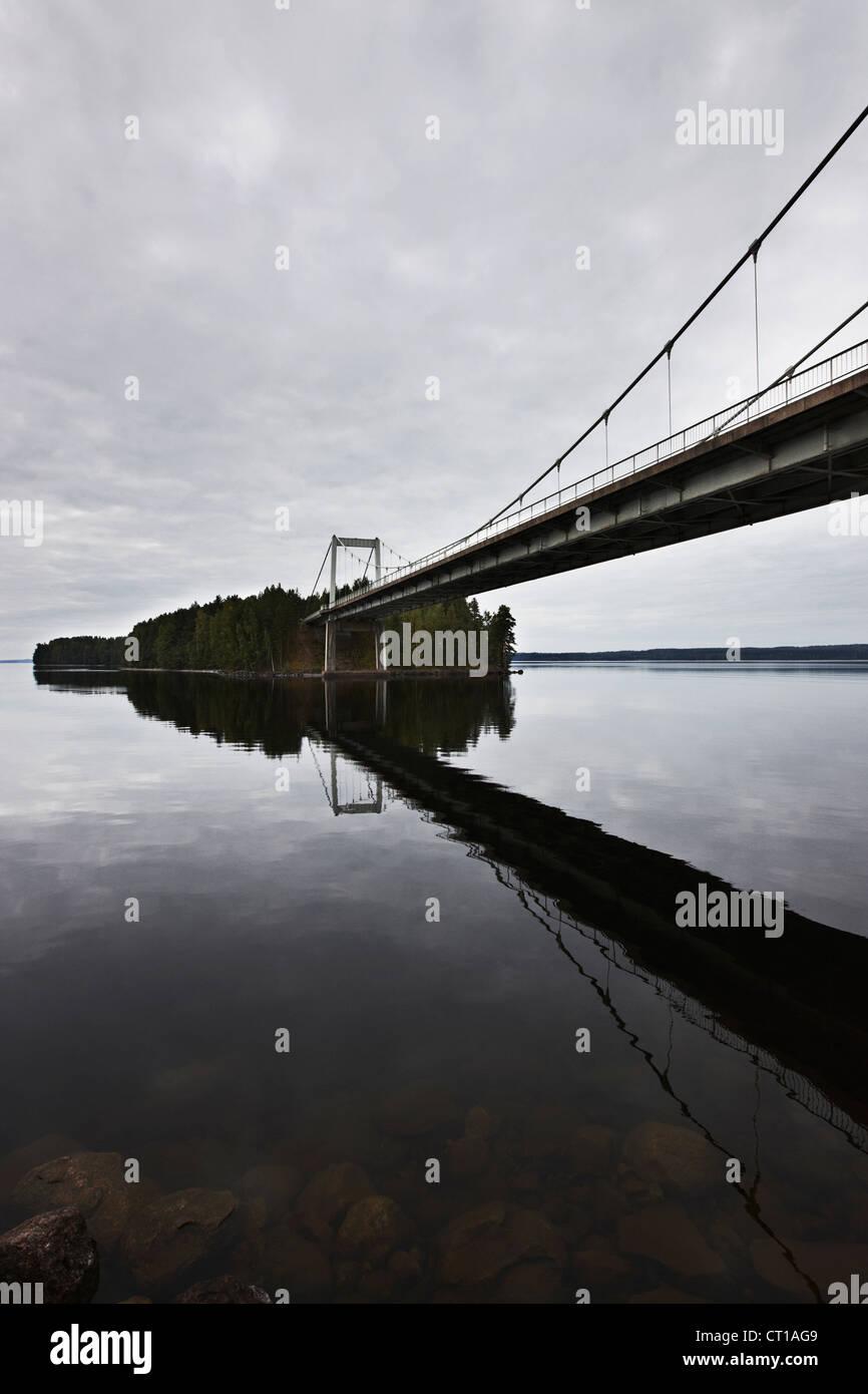 Bridge reflected in still lake - Stock Image