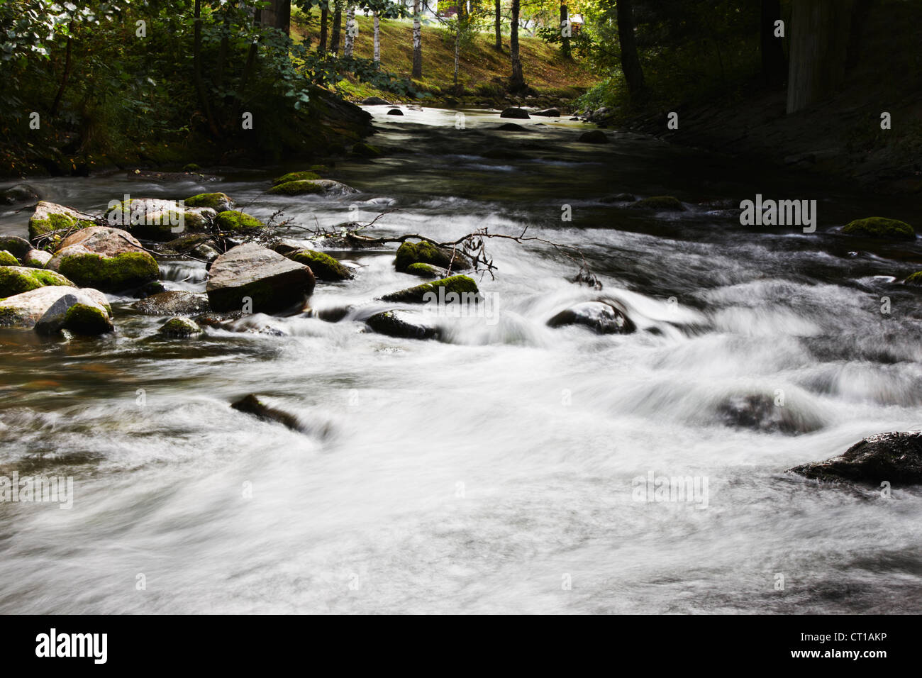 Blurred view of river rushing over rocks - Stock Image