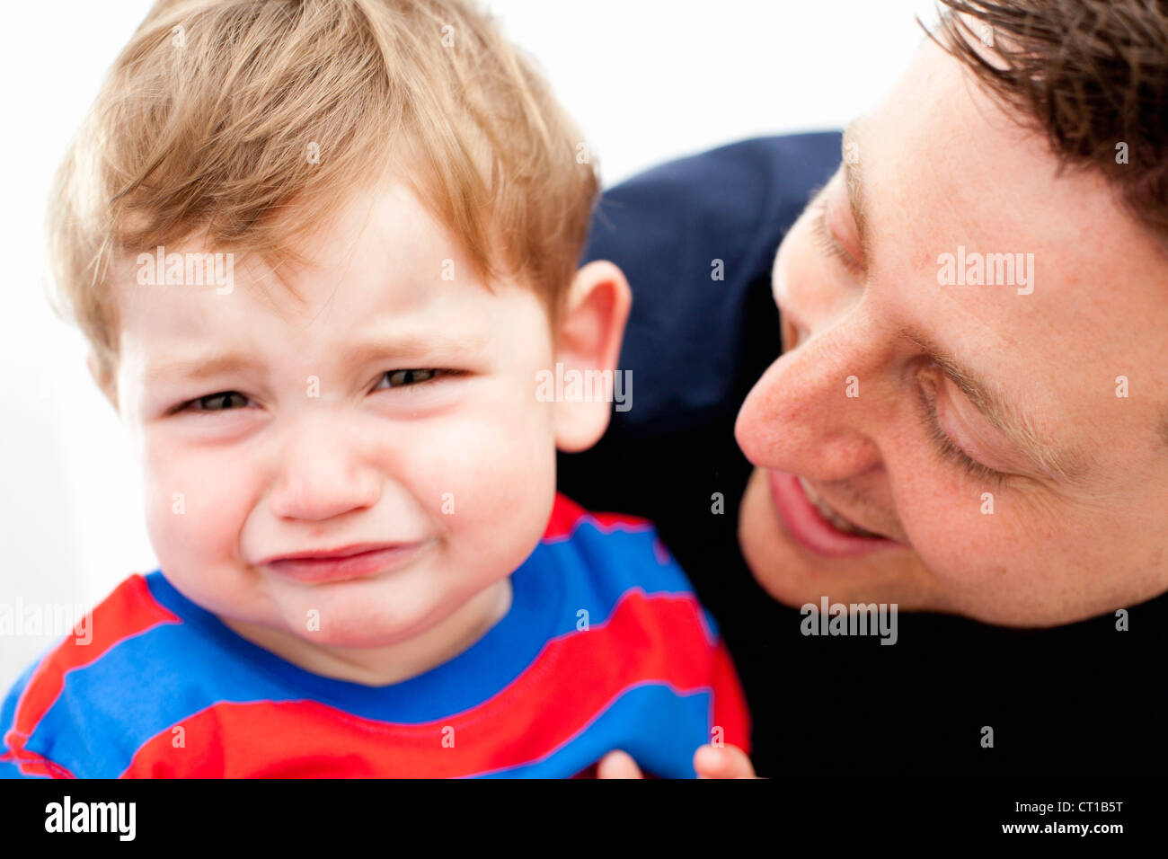 Father comforting crying son - Stock Image