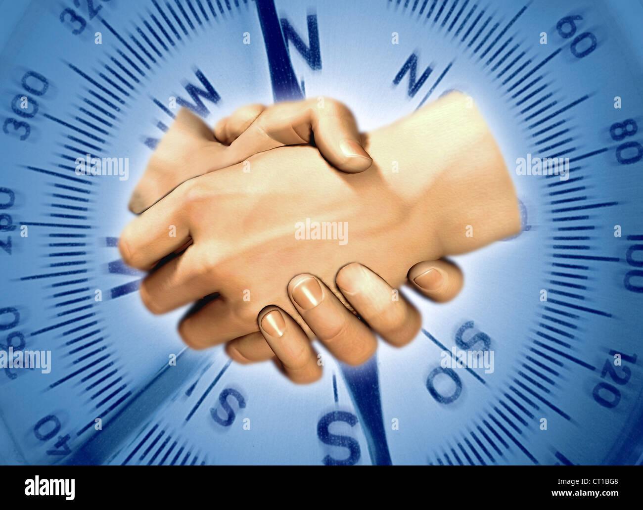 shake hands in front of a compass scale - 2 Hände reichen sich die Hand vor einem Kompass im Hintergrund Stock Photo