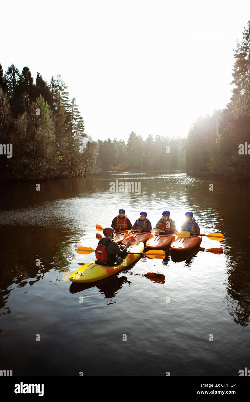 Teacher talking to students in kayaks Stock Photo