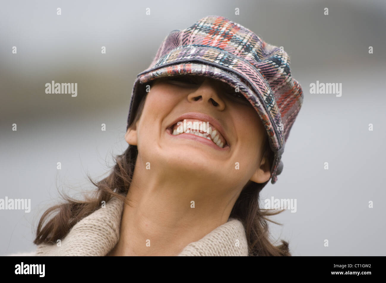 Smiling woman peering from under cap - Stock Image