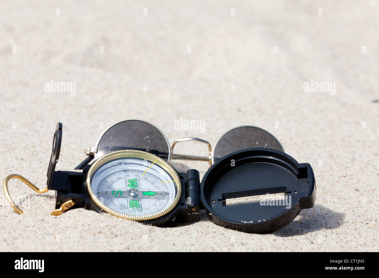 A compass and sunglasses lying on the hot desert sand - Stock Image
