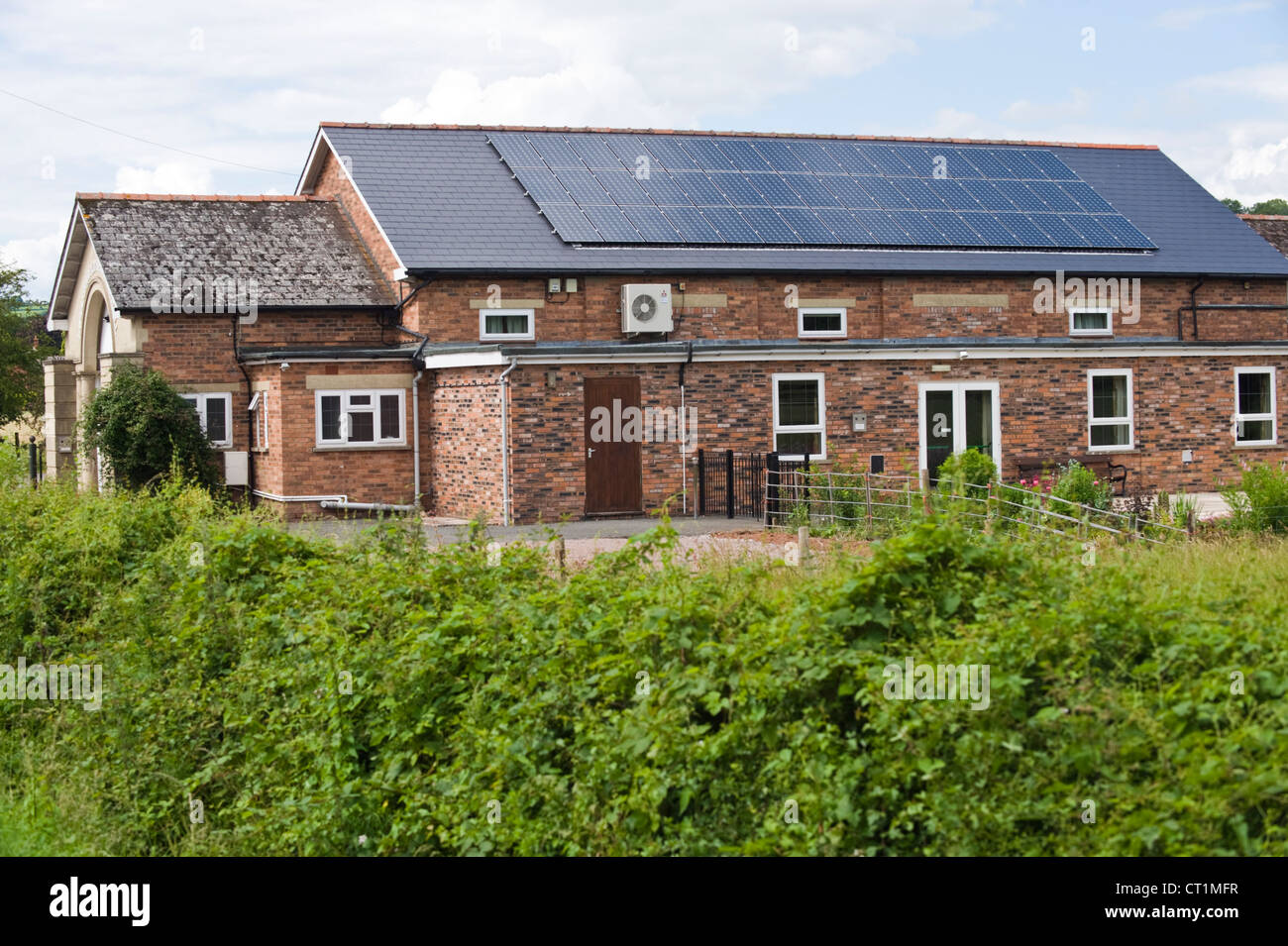 Solar panels on roof of community Memorial Hall in village of Ewyas Harold Herefordshire England UK - Stock Image